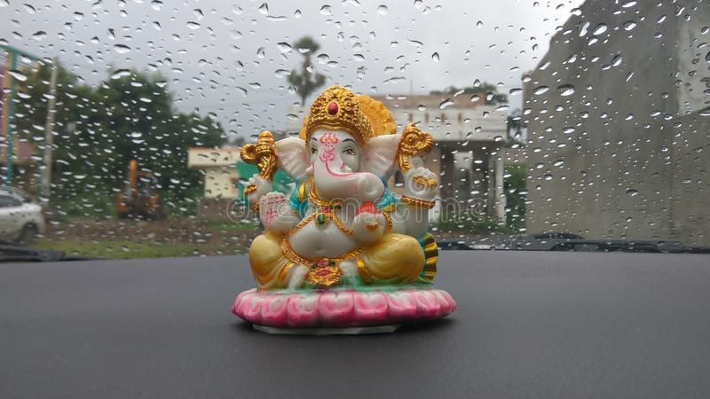 L'idole de Lord Ganesha dans la voiture avec la pluie a dessiné le fond photo stock