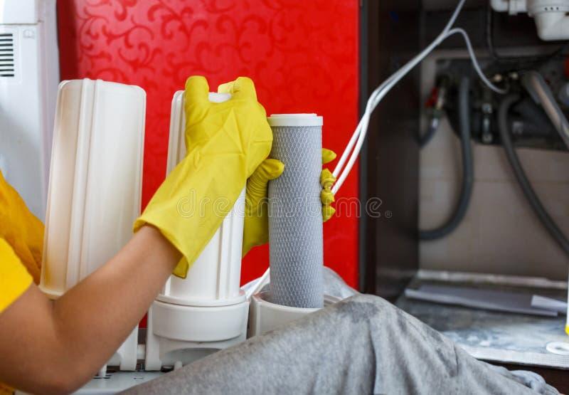 L'idraulico alto vicino nei cambiamenti gialli dei guanti della famiglia innaffia i filtri Cartucce di filtro cambianti dall'acqu fotografia stock