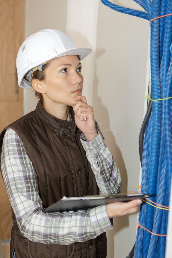 L'idraulico femminile che controlla la canalizzazione di un corso d'acqua convoglia il cantiere fotografie stock libere da diritti