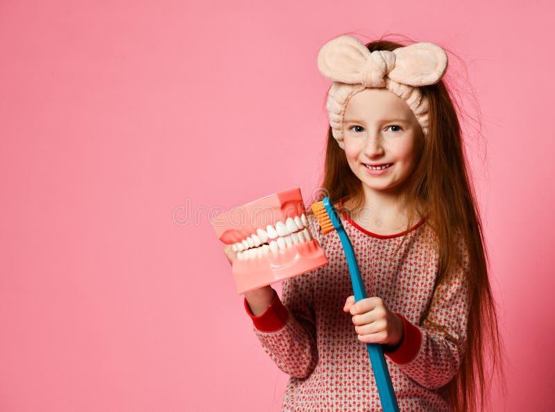 L'igiene dentale piccola ragazza sveglia felice con gli spazzolini da denti immagine stock libera da diritti