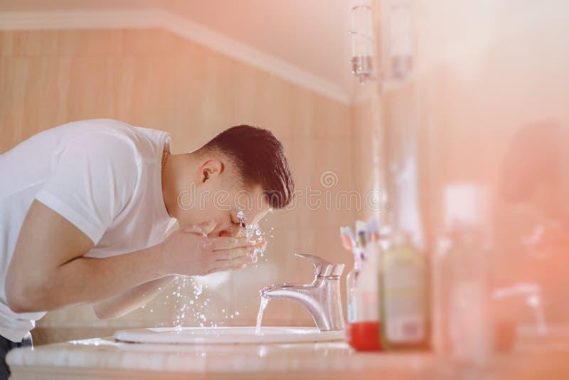 L'igiene di mattina, il ragazzo è lavata in un lavabo con spruzzo dell'acqua fotografia stock libera da diritti