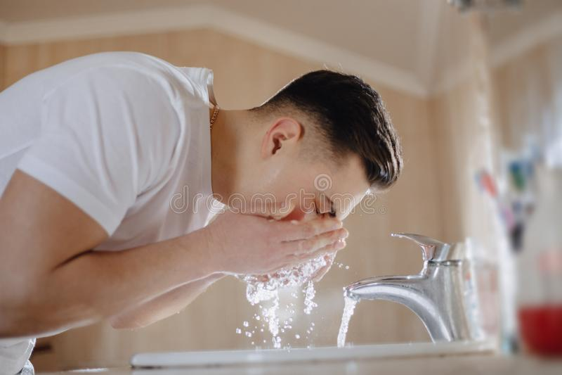 L'igiene di mattina, il ragazzo è lavata in un lavabo con spruzzo dell'acqua immagine stock