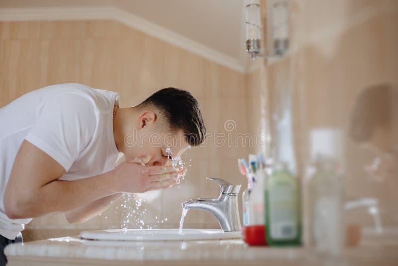 L'igiene di mattina, il ragazzo è lavata in un lavabo con spruzzo dell'acqua fotografia stock