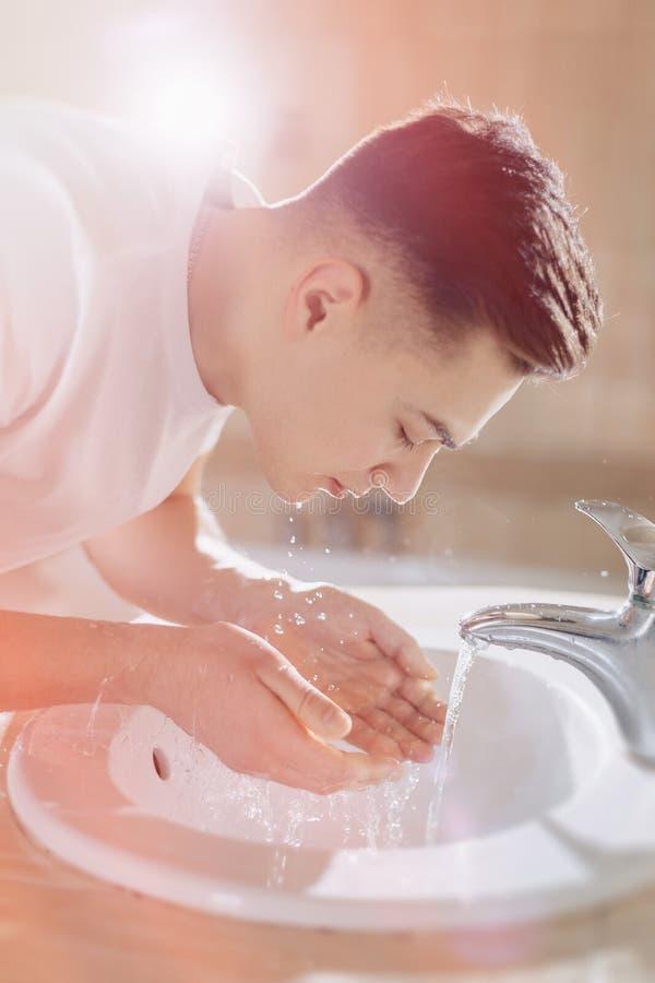 L'igiene di mattina, il ragazzo è lavata in un lavabo con spruzzo dell'acqua fotografie stock libere da diritti