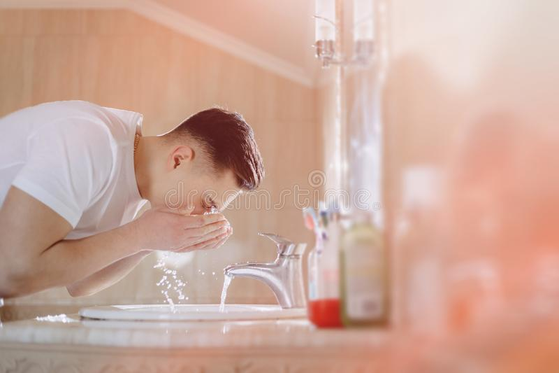 L'igiene di mattina, il ragazzo ? lavata in un lavabo con spruzzo dell'acqua fotografia stock libera da diritti