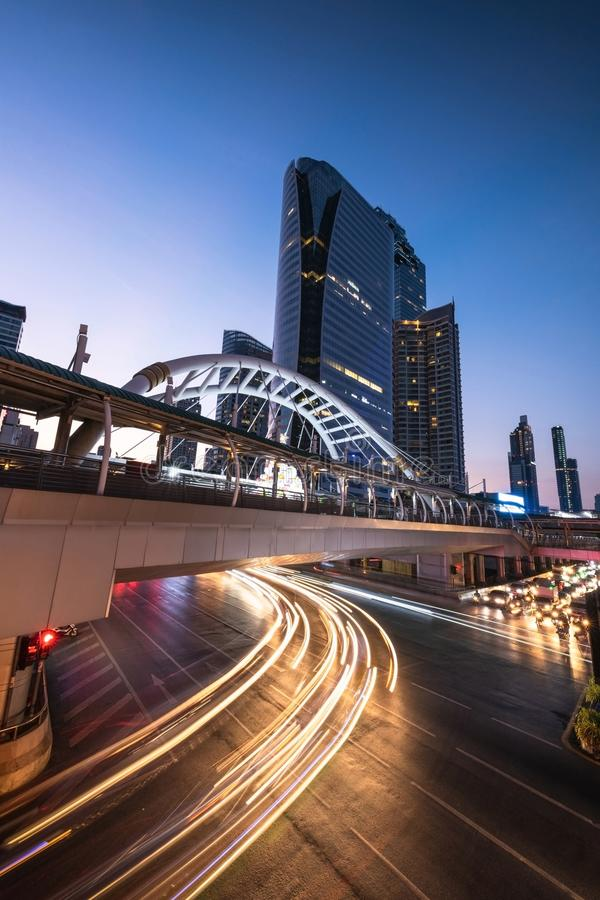 L'illuminazione notturna mostra il progetto architettonico dello skywalk sopra l'intersezione sulla strada di Sathorn a Bangkok, immagine stock