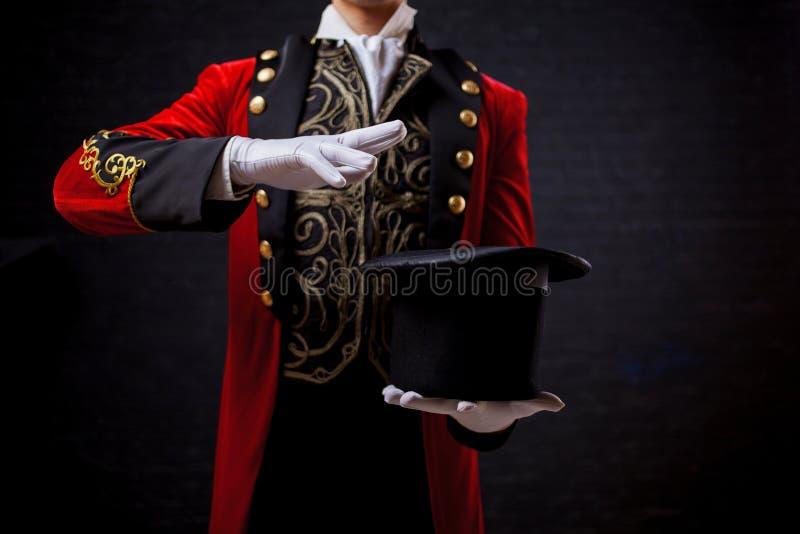 L'illusionniste de magicien, plan rapproché de main dans les gants, prises le cylindre dans des ses mains, ondulent vos mains photo stock