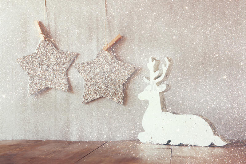 L'image abstraite du renne en bois blanc et du scintillement tient le premier rôle accrocher sur la corde au-dessus du fond d'arg photo stock