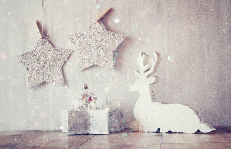 L'image abstraite du renne en bois blanc et du scintillement tient le premier rôle accrocher sur la corde au-dessus du fond d'arg photo libre de droits