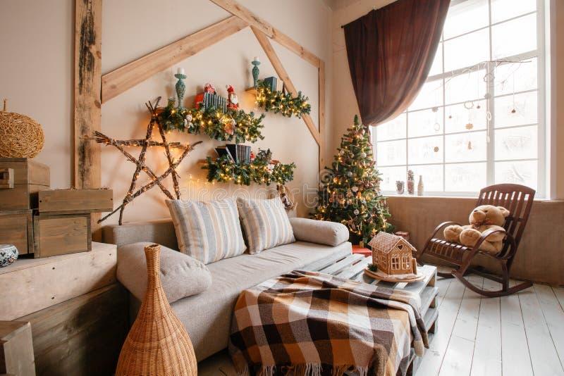 L'image calme du salon à la maison moderne intérieur a décoré l'arbre de Noël et les cadeaux, sofa, table couverte de couverture photos libres de droits