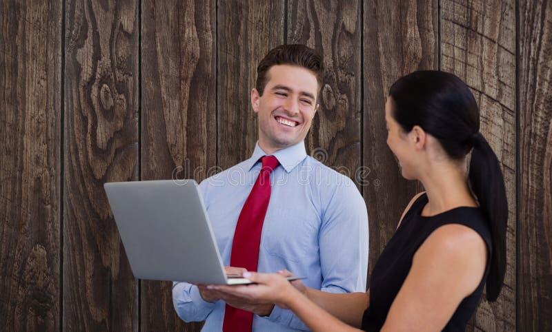 L'image composée de l'homme d'affaires et la femme d'affaires tiennent un ordinateur portable image stock