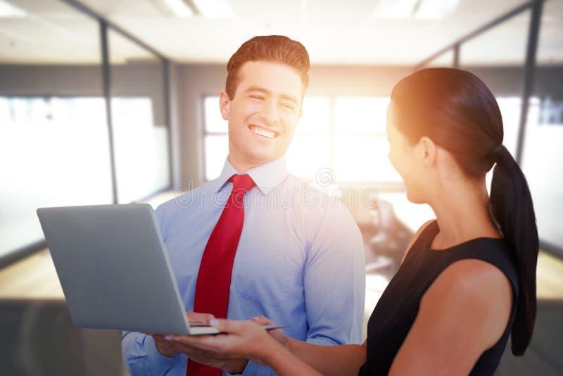 L'image composée de l'homme d'affaires et la femme d'affaires tiennent un ordinateur portable images stock