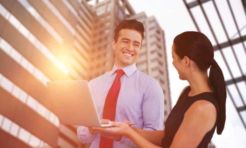L'image composée de l'homme d'affaires et la femme d'affaires tiennent un ordinateur portable photographie stock