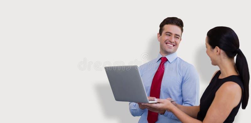 L'image composée de l'homme d'affaires et la femme d'affaires tiennent un ordinateur portable photos libres de droits