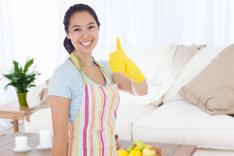 L'image composée de la femme dans le nettoyage vêtx renoncer à des pouces photographie stock libre de droits
