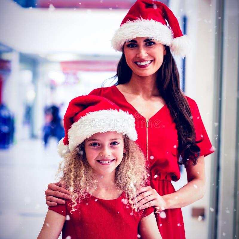 L'image composée du portrait de la mère et la fille dans Noël attire la position avec des cadeaux photographie stock