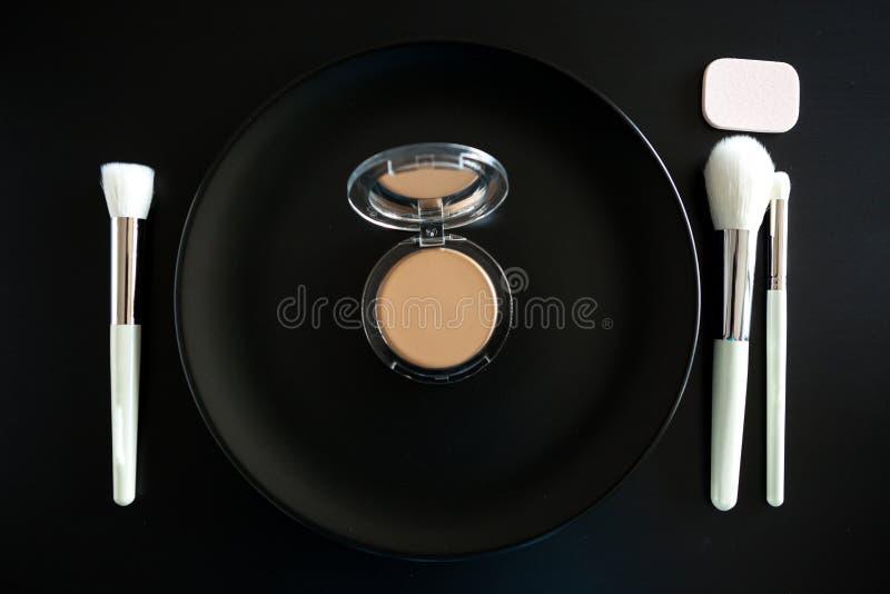 L'image conceptuelle de composent des brosses à côté du plat de dîner images stock