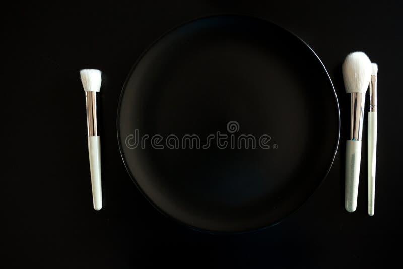 L'image conceptuelle de composent des brosses à côté du plat de dîner photos libres de droits
