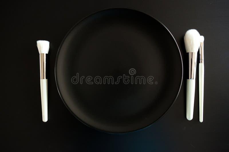L'image conceptuelle de composent des brosses à côté du plat de dîner photo stock