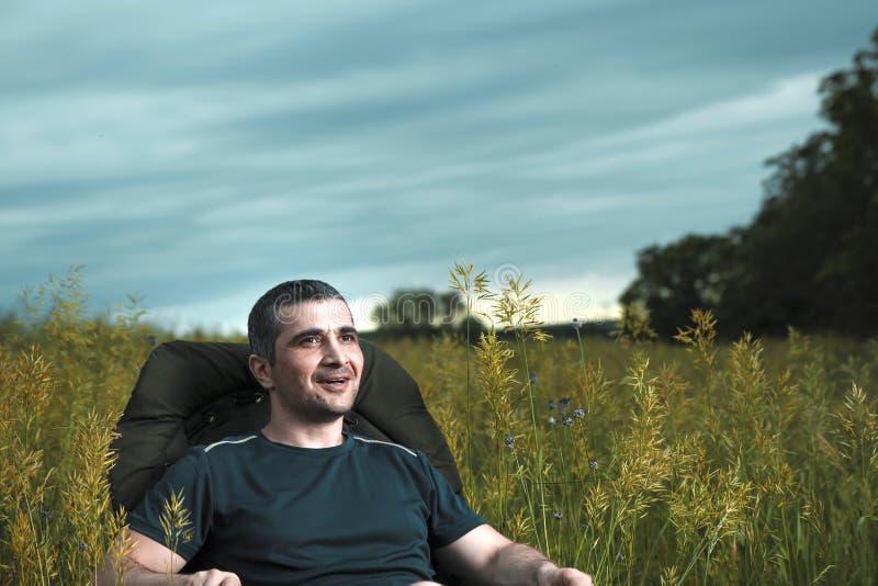 L'image conceptuelle des films de observation en technologies modernes, un jeune homme se repose dans une chaise confortable sur  images stock