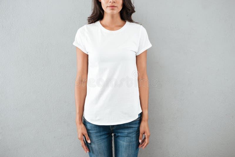 L'image cultivée d'une jeune femme s'est habillée dans le T-shirt photos stock