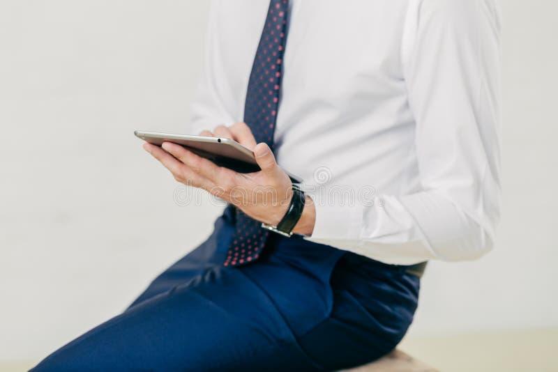 L'image cultivée de l'homme d'affaires prospère réussi dans la chemise blanche, pantalons noirs, lien, comprimé moderne de prises photos stock