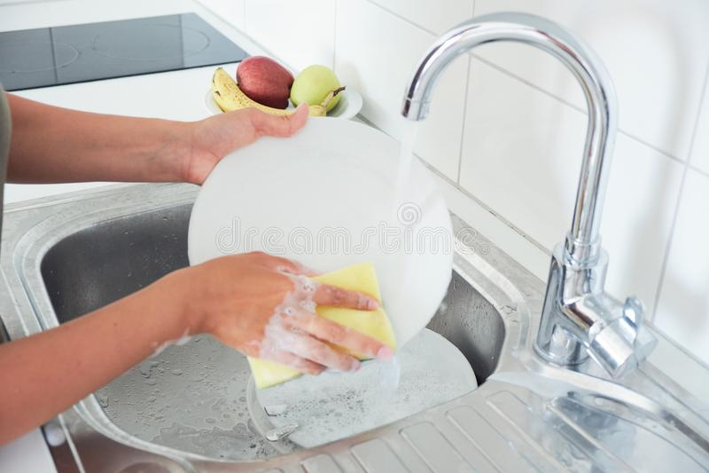 L'image cultivée de la jeune femme attirante lave des plats tout en faisant le nettoyage à la maison images libres de droits