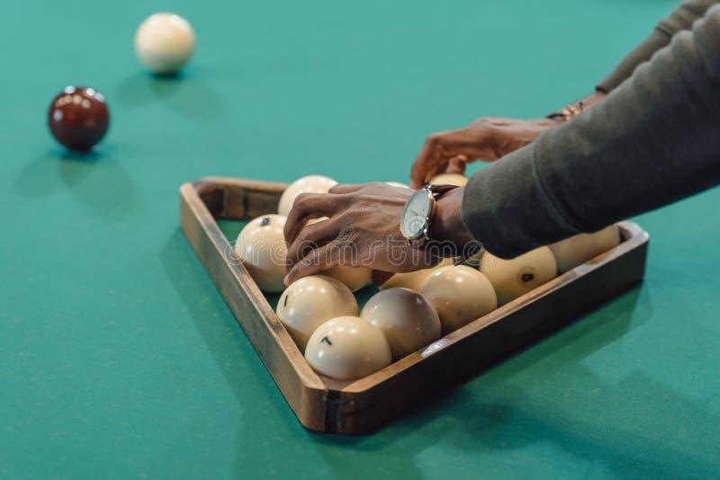 l'image cultivée des mains masculines formant des boules a placé par la triangle sur la piscine jouant photos stock