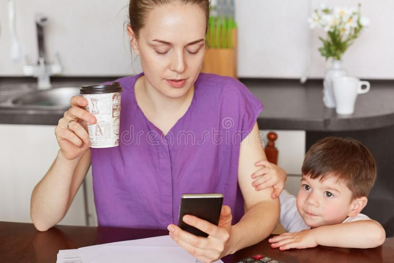 L'image cultivée du main-d'œuvre féminine concentré effectue le travail à distance, messages avec l'employé au téléphone portable image stock