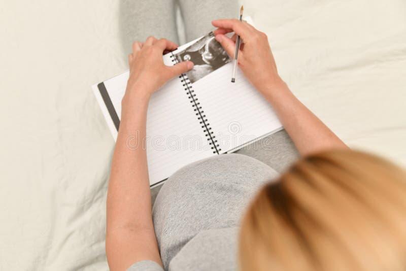 L'image d'ultrason de participation de femme enceinte et fait les notes dans un carnet Attente d'un enfant photo libre de droits