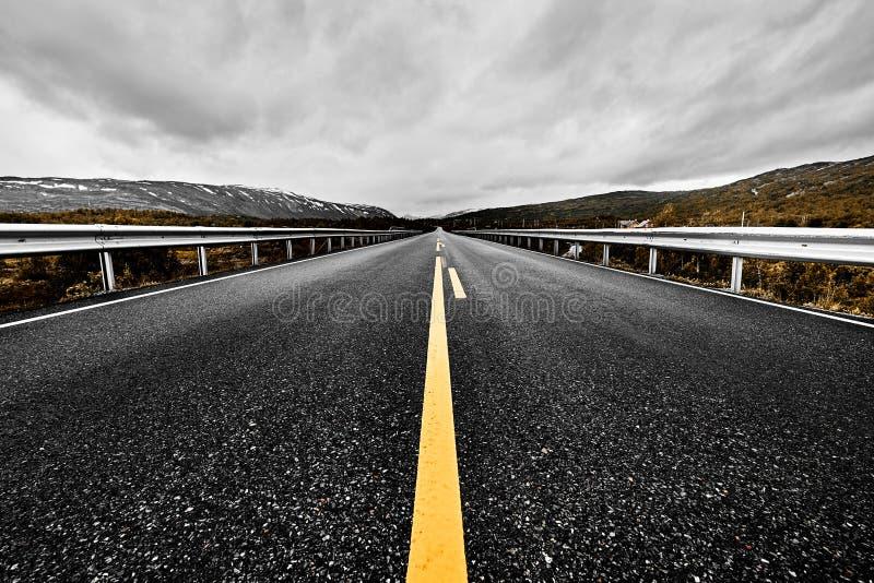 L'image d'une prairie grande ouverte et des montagnes avec une route pavée de route s'étendant jusque l'oeil peut voir avec le be photographie stock