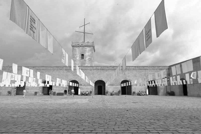 L'image de B&W de la cour intérieure décorée des drapeaux blancs et la tour de montre de Montjuic se retranchent, Barcelone, Cata photo stock