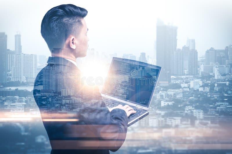 L'image de double exposition de l'homme d'affaires à l'aide d'un ordinateur portable pendant le lever de soleil a recouvert avec  photographie stock libre de droits