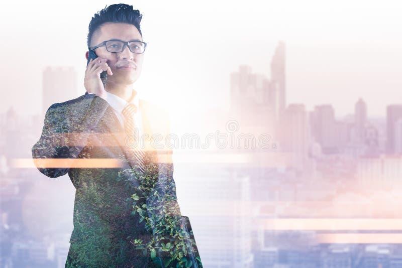 L'image de double exposition de l'homme d'affaires à l'aide d'un smartphone pendant le lever de soleil recouvert avec l'image de  illustration stock