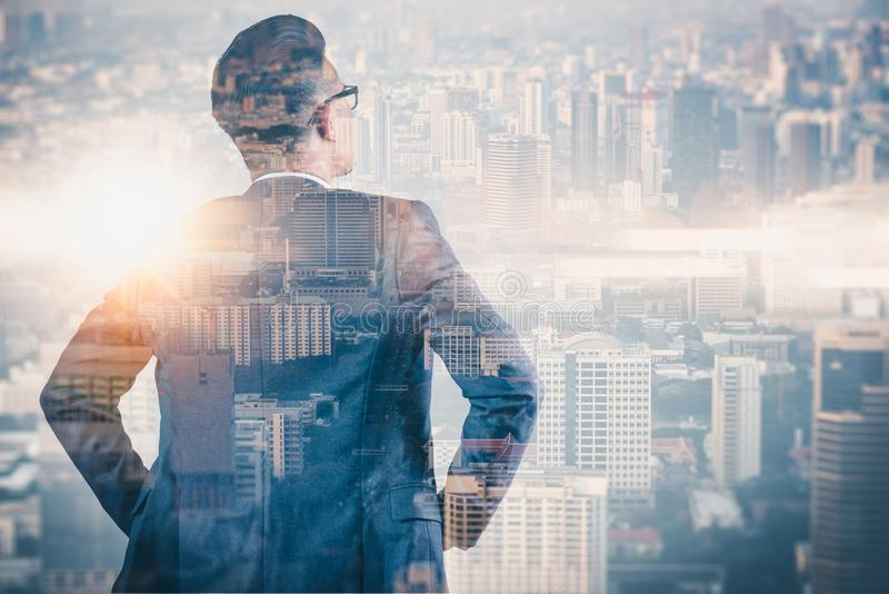 L'image de double exposition de l'homme d'affaires reculant pendant le lever de soleil recouvert avec l'image de paysage urbain L photos libres de droits