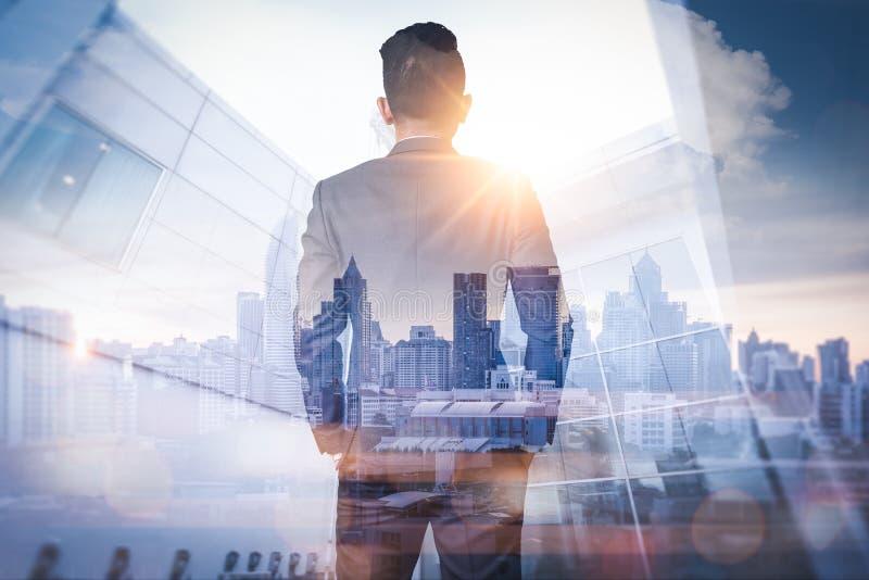 L'image de double exposition de l'homme d'affaires reculant pendant le lever de soleil recouvert avec l'image de paysage urbain L photographie stock libre de droits