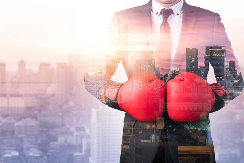 L'image de double exposition de l'homme d'affaires utilisant un recouvrement de boxe de gants avec l'image de paysage urbain le c photos stock