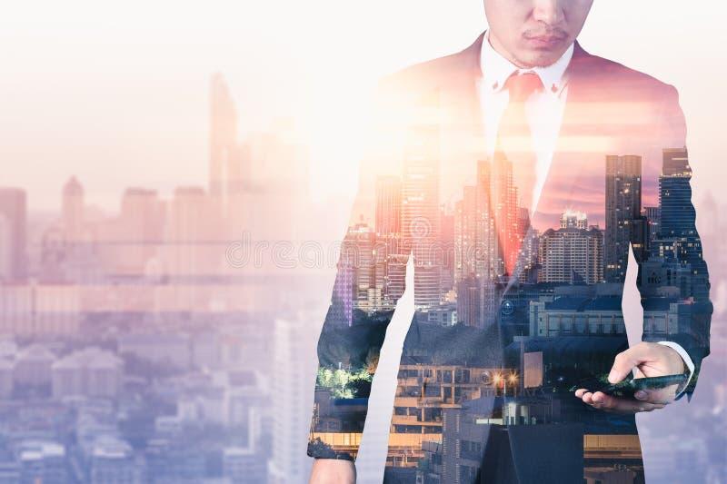 L'image de double exposition de l'homme d'affaires utilisant un smartphone pendant le lever de soleil a recouvert avec l'image de photographie stock libre de droits