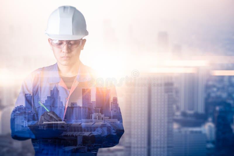 L'image de double exposition de la position d'ingénieur pendant le lever de soleil recouvert avec l'image de paysage urbain Le co images stock