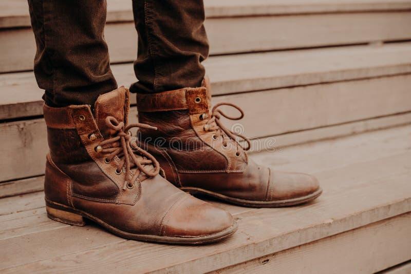 L'image de homme la position brune de chaussures sur des étapes en bois Mâle dans les pantalons et des chaussures hirsutes sur le photos stock