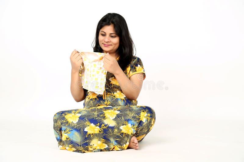 L'image de la dame enceinte tient le tissu de bébé à disposition avec le visage de sourire et se repose sur le plancher photos stock
