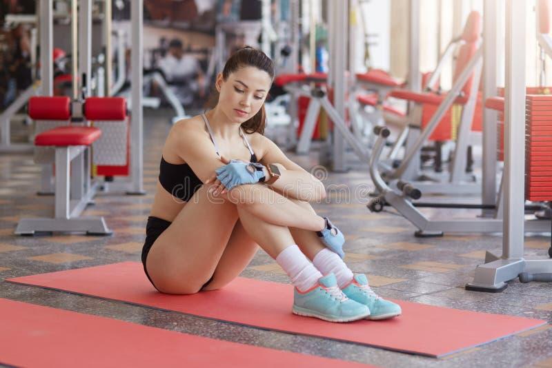 L'image de la femme d?contract?e de forme physique avec la figure parfaite se repose sur le tapis d'exercice, regardant pensiveme photo libre de droits