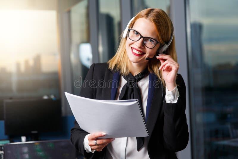 L'image de la femme de sourire avec des verres et les écouteurs avec le papier dans des mains s'approchent du mur de verre photo stock