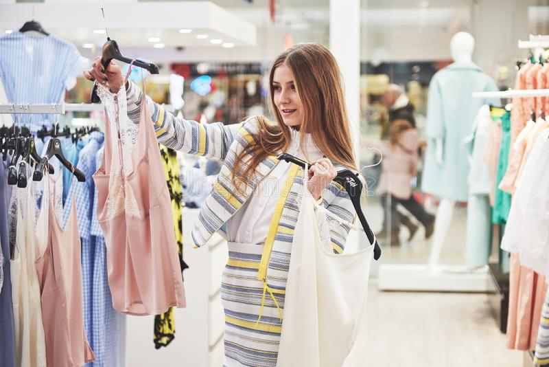 L'image de la jeune dame se tenant dans la boutique de vêtements choisissant à l'intérieur s'habille Regard de côté photographie stock
