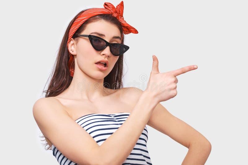 L'image de la jeune femme stupéfaite de brune dans des lunettes de soleil à la mode, indique de côté avec l'index pour masquer l' images libres de droits