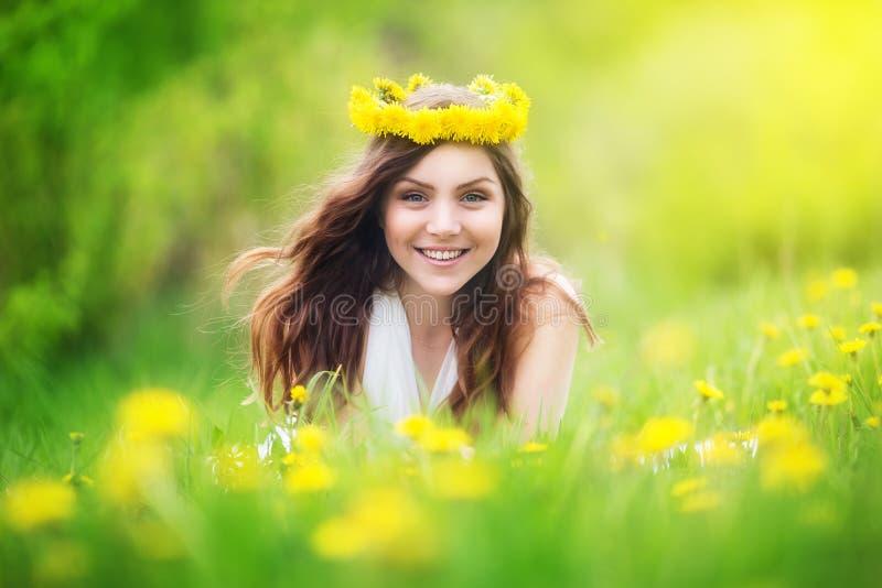 L'image de la jolie femme se couchant sur des pissenlits mettent en place, che heureux photos stock