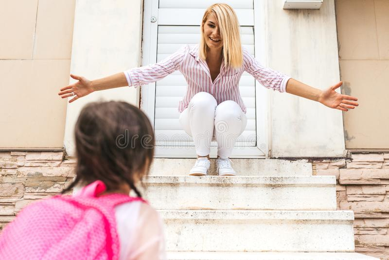 L'image de la mère heureuse avec des bras grands ouverts rencontre sa fille d'élève retournant à la maison du jardin d'enfants Bo images stock
