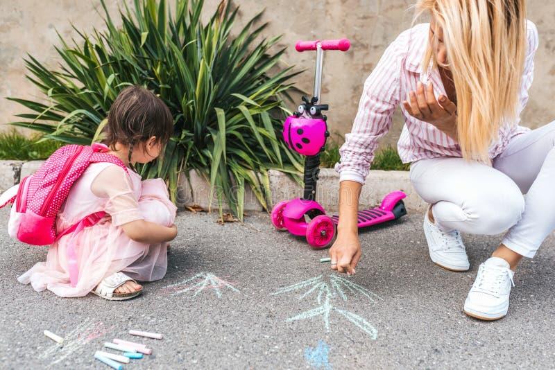 L'image de la petite fille heureuse porte le dessin rose de robe et de mère avec les craies colorées sur le trottoir Jeu femelle  photo libre de droits