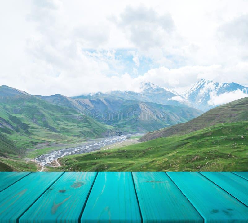L'image de la table en bois devant le résumé a brouillé le fond de la montagne peuvent être employés pour l'affichage ou le monta image libre de droits