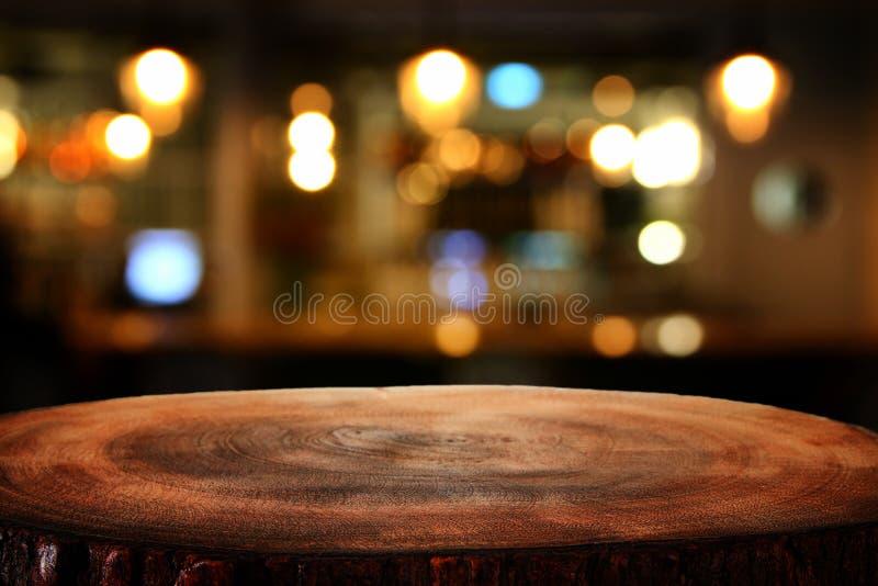 L'image de la table en bois devant le résumé a brouillé le fond de lumières de restaurant photographie stock libre de droits